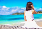 Young woman talking on phone during tropical beach vacation — Stock Photo