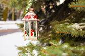 Christmas lantern with snowfall hanging on a fir branch — Stock Photo