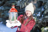 Young happy woman with red Christmas lantern in the snow — Stock Photo