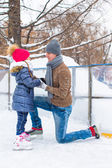 Happy family on skating rink outdoors — Stock Photo