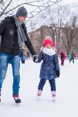 Adorable little girl and happy dad on skating rink outdoor — Foto Stock