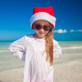 Little adorable girl in red Santa hat at tropical beach — Stok fotoğraf