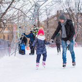 Adorable little girl and happy father on skating rink outdoor — Stock Photo