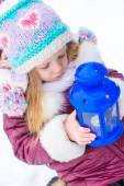 Little cute girl warms her hands on candle in blue lantern in winter time — Stock Photo