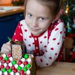 Little adorable girl decorating gingerbread house for Christmas — Stock Photo #63836629