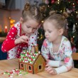 Little adorable girls decorating gingerbread house for Christmas — Stock Photo #63836739