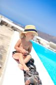 Adorable little girl near pool during greek vacation in Santorini — Stock Photo