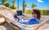 Young man working with laptop in hammock during beach vacation — Stock Photo