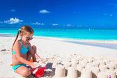 Menina brincando com brinquedos de praia durante as férias tropicais — Fotografia Stock