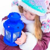 Adorable little girl holding Christmas lantern outdoors on beautiful winter snow day — Stock Photo