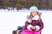 Adorable little happy girl sledding in winter snowy day — Stock Photo