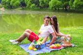 Young happy couple picnicking outdoors — Stock Photo
