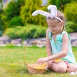 Adorable little girl wearing bunny ears holding basket with Easter eggs — Stock Photo #64870321
