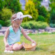 Adorable little girl wearing bunny ears holding basket with Easter eggs — Stock Photo #64874571