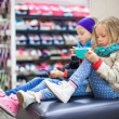Little girls tired while doing shopping in shopping center — Stock Photo #64874399
