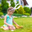Adorable little girl wearing bunny ears holding basket with Easter eggs — Stock Photo #64874563