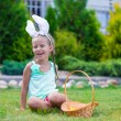 Adorable little girl wearing bunny ears holding basket with Easter eggs — Stock Photo #64874847