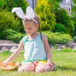 Adorable little girl wearing bunny ears holding basket with Easter eggs — Stock Photo #64874915