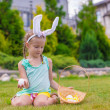 Adorable little girl wearing bunny ears holding basket with Easter eggs — Stock Photo #64874991
