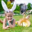 Adorable little girl wearing bunny ears holding basket with Easter eggs — Stock Photo #64875041