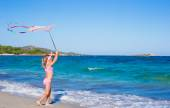 Little happy girl playing with flying kite during tropical beach vacation — Foto de Stock