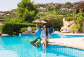 Happy young romantic couple relaxing near swimming pool — Stock Photo