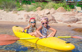 Little adorable girls enjoying kayaking on yellow kayak — Stock Photo