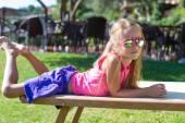 Schattig meisje op strand ligstoel buitenshuis — Stockfoto