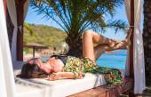 Young beautiful woman relaxing on beach bed during tropical vacation — Stock Photo