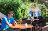 Young man in outdoor cafe talking on cellphone — Stock Photo