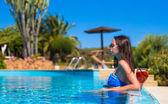 Mooie jonge vrouw ontspannen in het zwembad met cocktail — Stockfoto