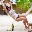 Happy young woman lying in hammock on tropical beach — Stock Photo #66956287