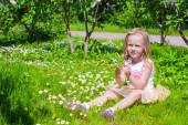 Little adorable girl enjoying beautiful day in blooming garden — Stock Photo