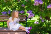 Little adorable girl near flowers in the garden — Photo