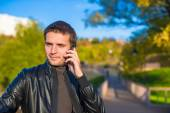 Young man with talking by phone outoors — Stock Photo