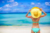 Beautiful woman in yellow hat on white tropical beach — Stock Photo