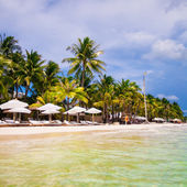 Beach chairs and umbrellas on exotic tropical white sandy beach — Stock Photo