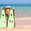 Little girl with flippers and goggles for snorkling on the beach — Stock Photo #68635895