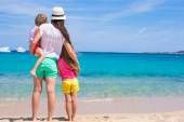 Young mom and little girls at white beach on sunny day — Stock Photo