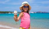 Little adorable girl with ice cream on tropical beach — Stock Photo