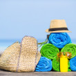 Beach and summer vacation accessories concept - close-up of colorful towels, hat, bag and sunblock — Stock Photo #70962087