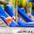 Tasty cocktail on wooden table near swimming pool — Stock Photo #70962903