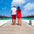 Young couple on tropical beach jetty at perfect island — Stock Photo #70963159