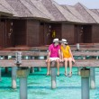 Young couple on tropical beach jetty near water bungalow — Stock Photo #70964847
