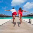 Young couple on tropical beach jetty at perfect island — Stock Photo #70964877