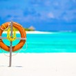 Lifebuoy ring on tropical white beach — Stock Photo #70965621