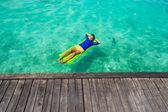 Joven descansando en un colchón inflable en el mar — Foto de Stock
