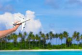 Small white toy airplane on tropical beach in human hand — Stock Photo