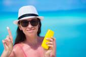 Young happy woman applying suntan lotion on her nose on white beach — Stockfoto