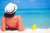 Beautiful young woman holding a suncream lying on tropical beach — Stock Photo
